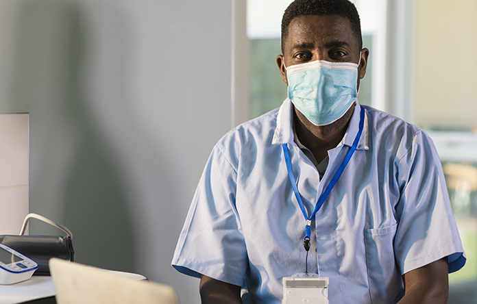 Male NHS worker wearing a face mask.